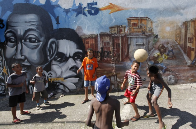 Children play in front of graffiti painted by artists of OPNI in the Vila Flavia favela of Sao Paulo